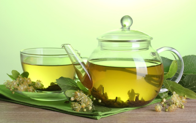 teapot and cup with linden tea and flowers on wooden table on green background