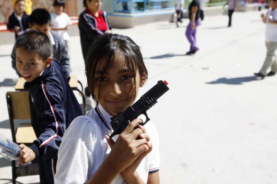 A school girl poses for a picture while holding a toy gun at a school in Ciudad Juarez